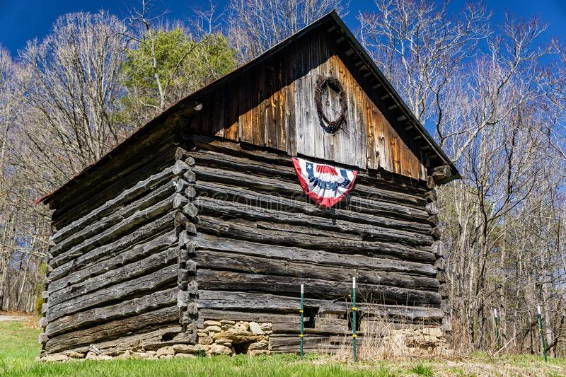 Log Barn with an American Banner royalty free stock image