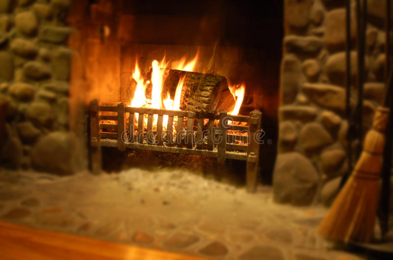 Log burning in stone fireplace. Log burning in stone, rustic fireplace or hearth stock image