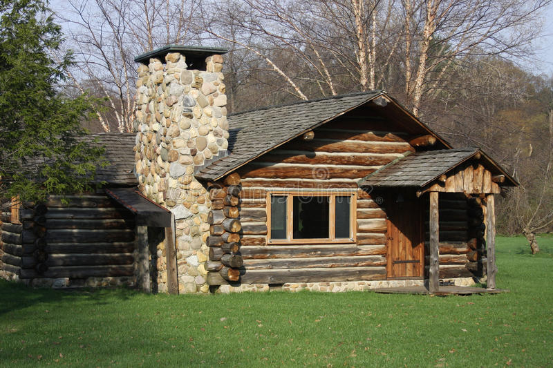 Log Cabin. Rustic log cabin with a natural fieldstone chimney in a rural country setting in upstate New York photographed during the springtime
