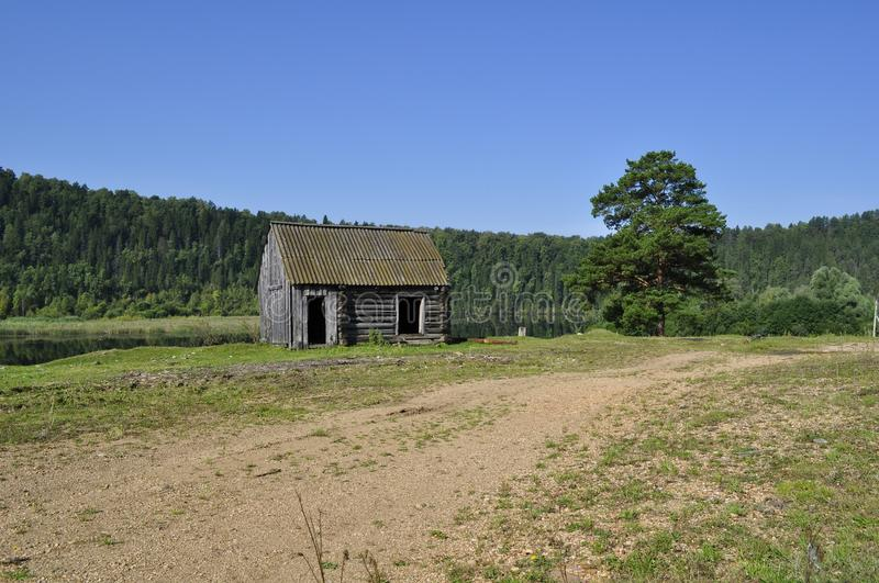Log cabin on the banks of the river stock photography