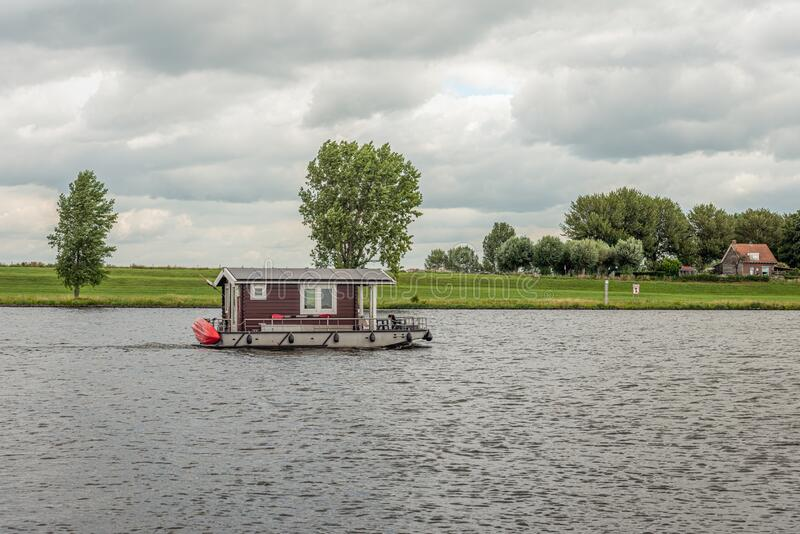 Log cabin boat sailing on a Dutch river royalty free stock image