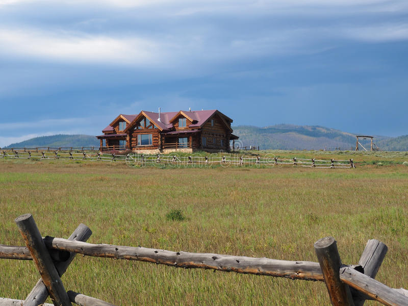 Log cabin home in Colorado. Log cabin home on a prairie in rural Colorado in the Rockie Mountains Preserve. Behind the home are mountains. The prairie is stock photo