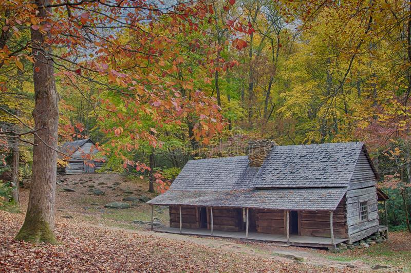 Log cabin and log barn among fall colors. Mountain log cabin homestead with colorful fall foliage with barn in up the hill surrounded by rocky ground royalty free stock photography