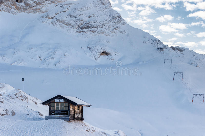 Log cabin and ski lift on a snow-covered mountain slope stock photography