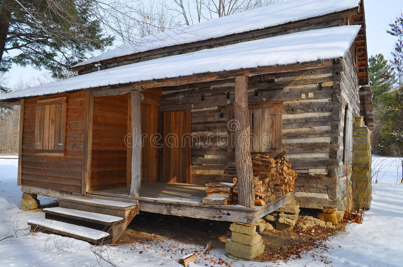 Log cabin in snow. Old log cabin with a small porch after a light winter snow royalty free stock photos