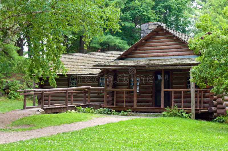 Log cabin in woods. Log cabin in a clearing in woods with a porch and handicap accessible ramp