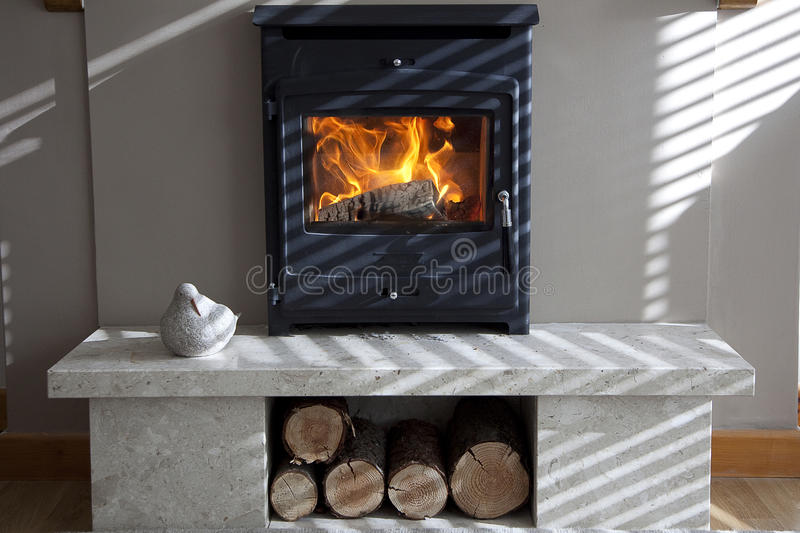 Log fire burning with evening shadows. Log burner fire in fireplace with evening sunlight through blinds causing shadows stock photos
