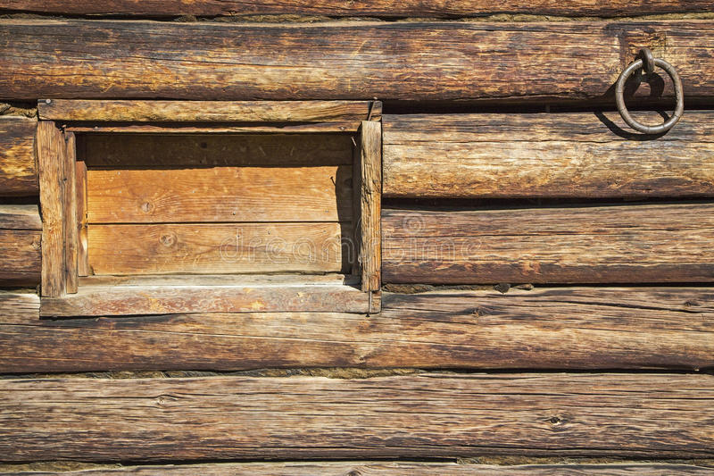 Log wall cinch ring tack grungy background. The wooden window and metal tack livestock cinch ring provides western wallpaper background on ranch barn royalty free stock images