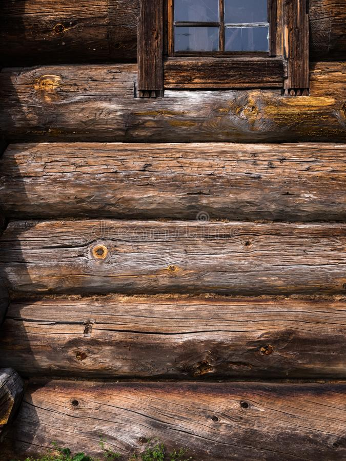 Log wall of rustic house with window. Wooden texture. Elements of an old rustic house made of wooden logs stock photo