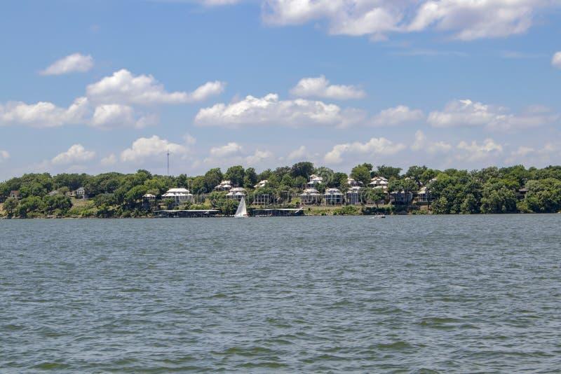 Logements près du lac parmi les arbres sous un ciel nuageux de blule avec un voilier et un ponton sur l'eau photos stock