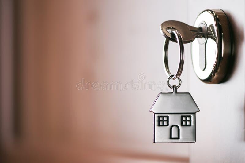 Logez la clé sur un porte-clés argenté formé par maison dans la serrure d'un entr photos stock