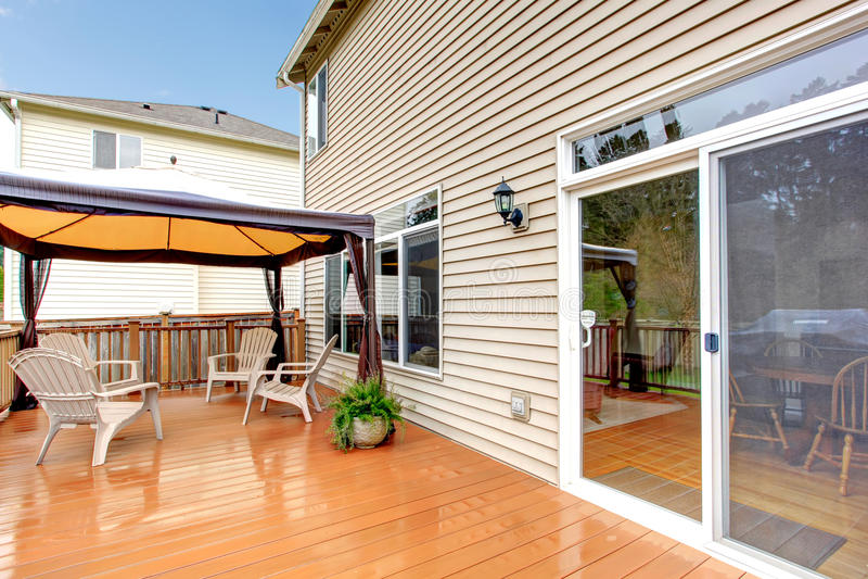 Logez le porche arrière avec le parapluie et les chaises pendant la pluie. photographie stock