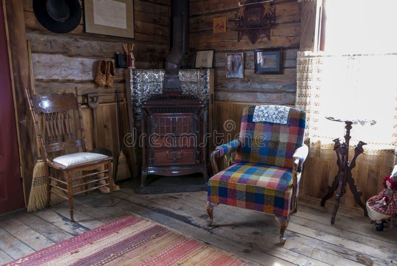 Logga kabinvardagsrum med stolar och spis royaltyfria bilder