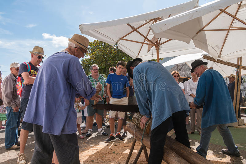 Loggers cut wood with a saw former lumberjack. Challans, France - August 11, 2016 : event Once Challans Autrefois Challans organized by the city and plunges stock photography