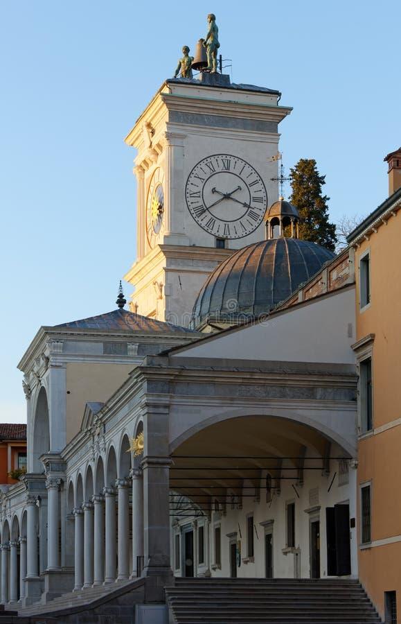 Loggia av det St James och klockatornet på solnedgången i Udine royaltyfria bilder