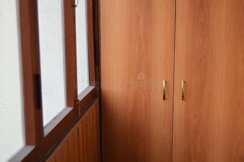 Logia esmaltada con el guardarropa de madera en el balcón, el sistema del almacenamiento y el concepto de seguridad y de seguro d imagen de archivo
