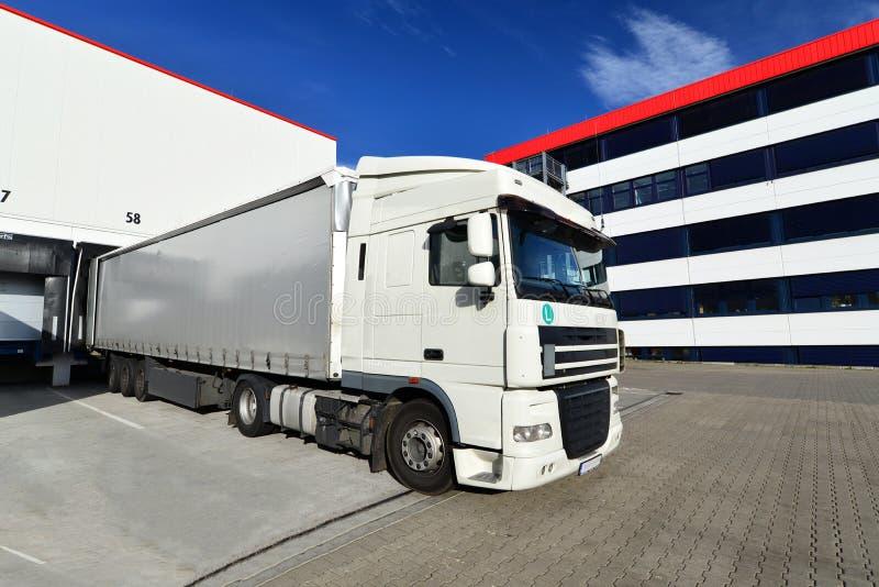 Logistiek en goederenopslag - lading en het leegmaken van goederen voor vervoer per vrachtwagen stock fotografie