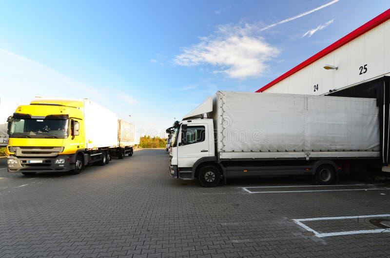 Logistiek en goederenopslag - lading en het leegmaken van goederen voor vervoer per vrachtwagen stock foto's