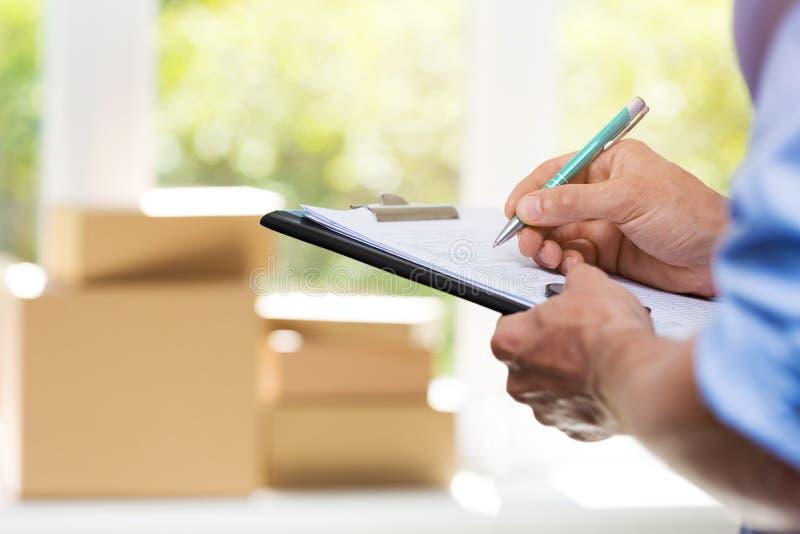 Logistik - Zustelldienst-Mannschreibensdokumente lizenzfreie stockbilder