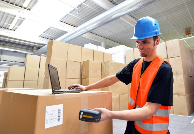 Logistikarbetare - mannen avläser jordlotter av gods och förbereder Det royaltyfri fotografi