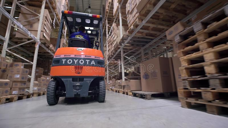 Logistyka biznes i wysyłki łatwość z ręcznego pracownika operacyjnym forklift ruszać się pudełka i towary, mężczyzna pracuje wewn zdjęcia royalty free