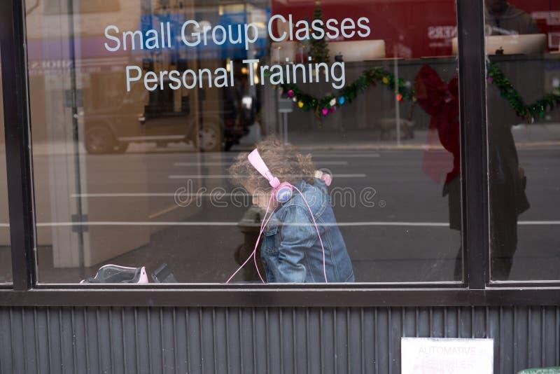 Logo Apple imac i grupperna som utbildar - barn med lyssnande musik för rosa hörlurar i en klassrumsutbildning i NYC arkivfoto