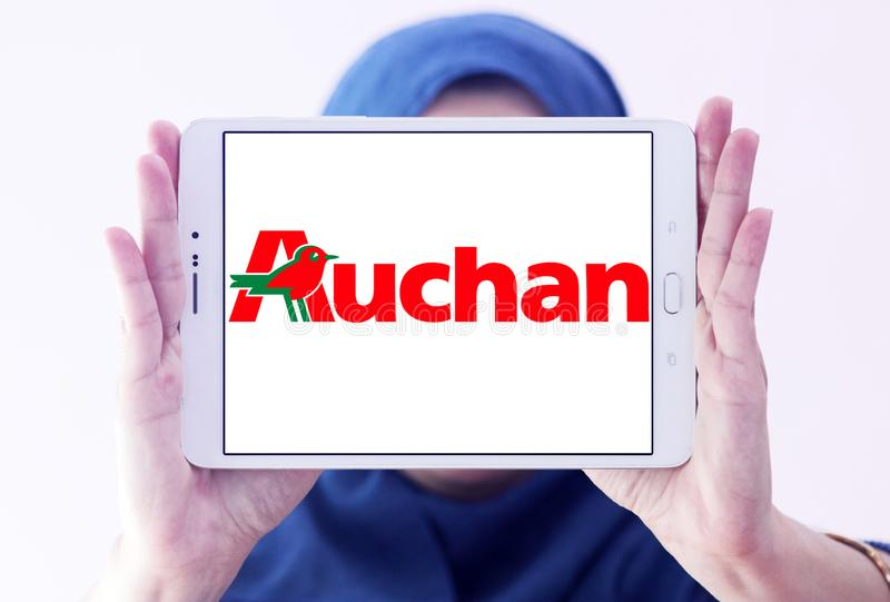Auchan retail group logo. Logo of Auchan retailer on samsung tablet holded by arab muslim woman. Auchan is a French international retail group and multinational stock image
