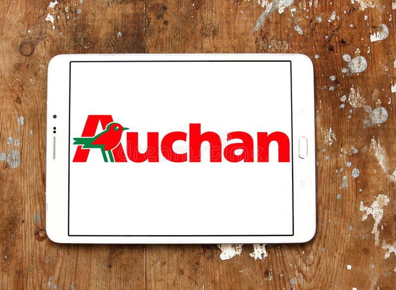 Auchan retail group logo. Logo of Auchan retailer on samsung tablet on wooden background. Auchan is a French international retail group and multinational stock photos