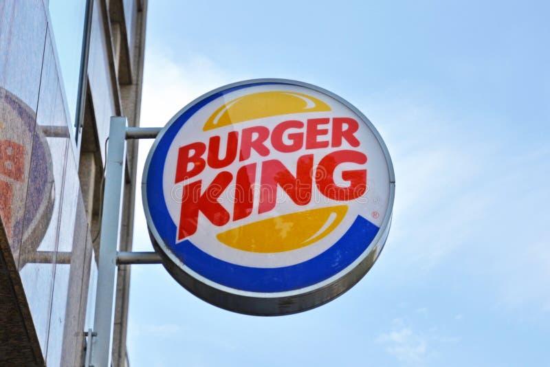 Logo av hamburgaresnabbmatkedjan 'Burger King 'som hänger utanför främst av blå himmel arkivfoto