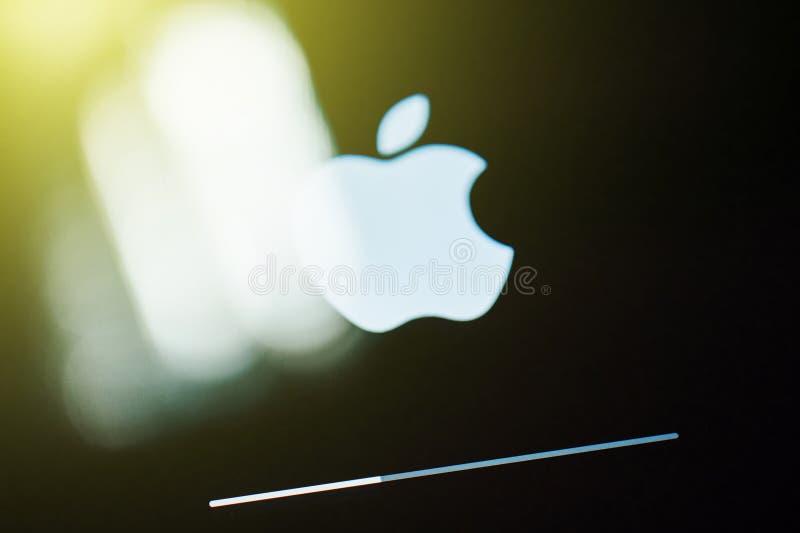 Logo bianco dei calcolatori Apple su visualizzatore digitale con la barra dell'aggiornamento immagine stock