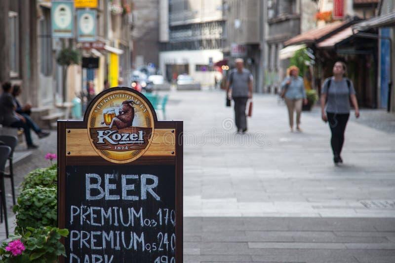 Logo de bière de Kozel dans une rue piétonnière avec les prix des différentes bières de la marque photos stock