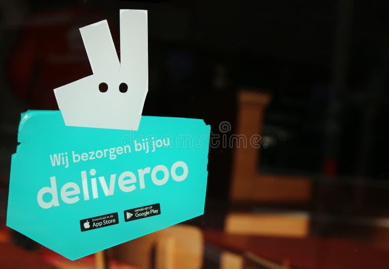 Logo de Deliveroo à une fenêtre d'un restaurant avec l'espace pour le texte sur un côté de l'image images stock