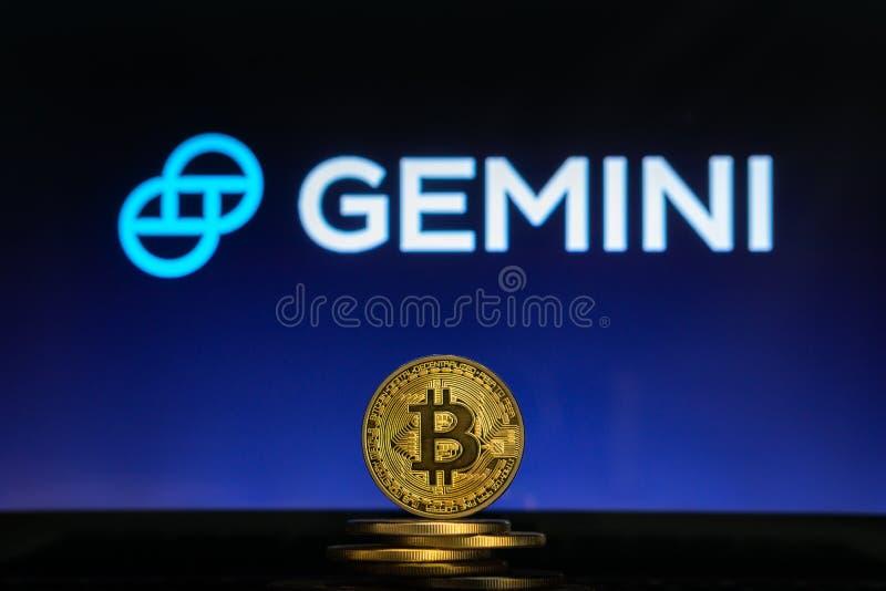 Logo dei Gemelli su uno schermo di computer con una pila di monete di cryptocurency di Bitcoin immagine stock
