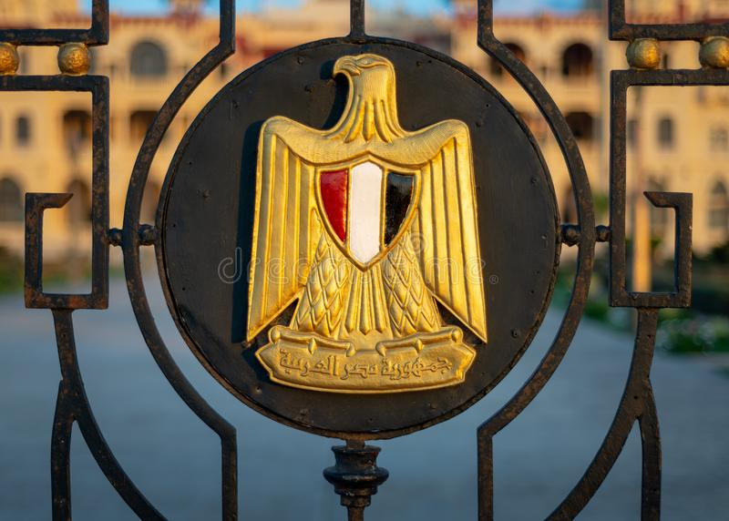 Logo, a Golden Eagle of Saladin holding a scroll with Arabic text Arab Republic of Egypt and a shield with the flag`s colors. Logo of Egypt on an iron fence stock images