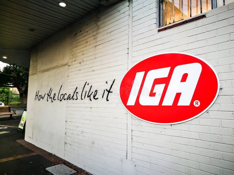 Logo för märke för IGA Australian supermarketgrupp på en vägg med slogan` hur lokalerna gillar den `, arkivbilder