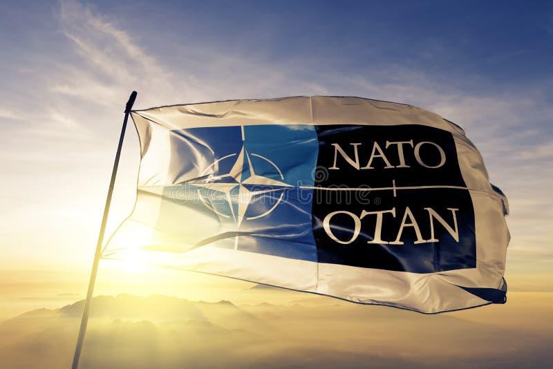 Logo för NATO OTAN för organisation för fördrag för norrAtlanten tyg för flaggatextiltorkduk som vinkar på den bästa soluppgångmi vektor illustrationer
