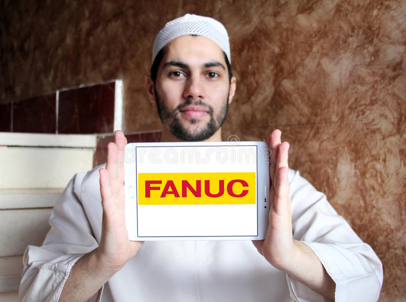 FANUC company logo. Logo of FANUC company on samsung tablet holded by arab muslim man. FANUC is the worldwide leader in factory automation technology royalty free stock photography