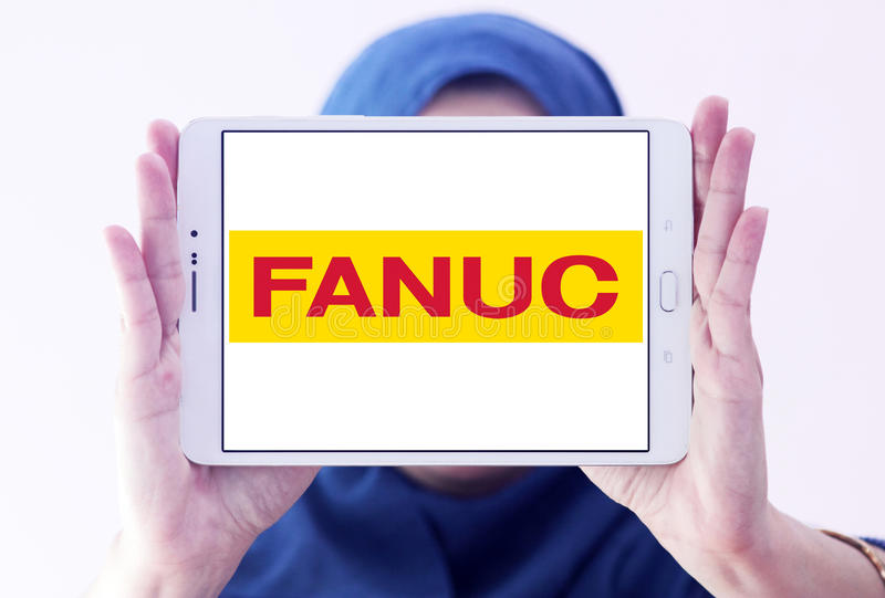 FANUC company logo. Logo of FANUC company on samsung tablet holded by arab muslim woman. FANUC is the worldwide leader in factory automation technology stock photos
