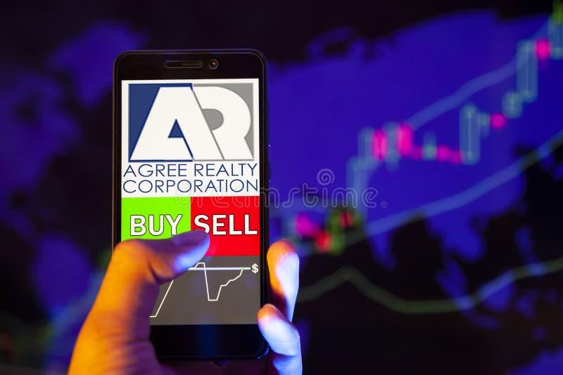 Logo firmy Agree Realty Corporation ADC na ekranie smartfona, ręka handlowca trzymającego telefon komórkowy z napisem KUP lub SPR zdjęcie royalty free
