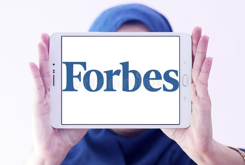Forbes magazine logo. Logo of Forbes magazine on samsung tablet holded by arab muslim woman. Forbes is an American business magazine. it features original royalty free stock photo