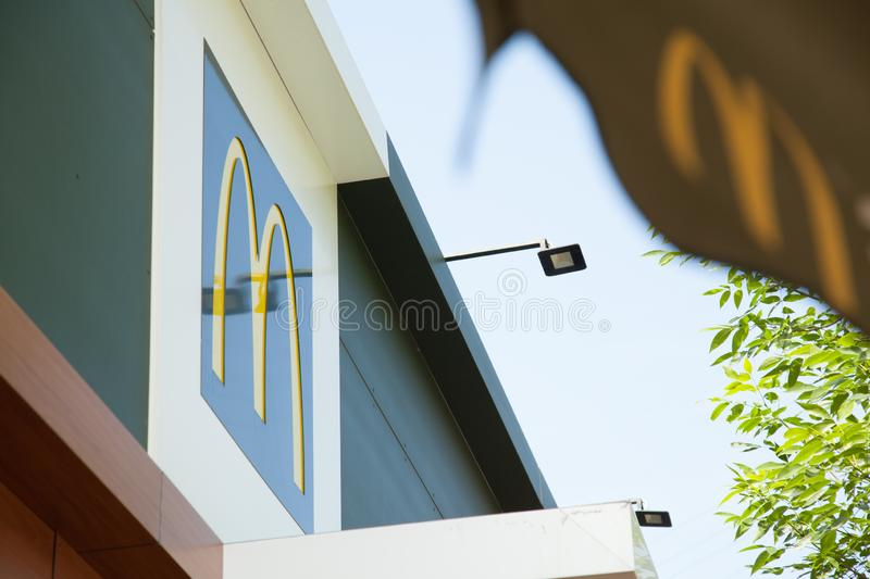 Logo of the letter M McDonald`s fast food restaurant on the roof of the building in a big city royalty free stock photo