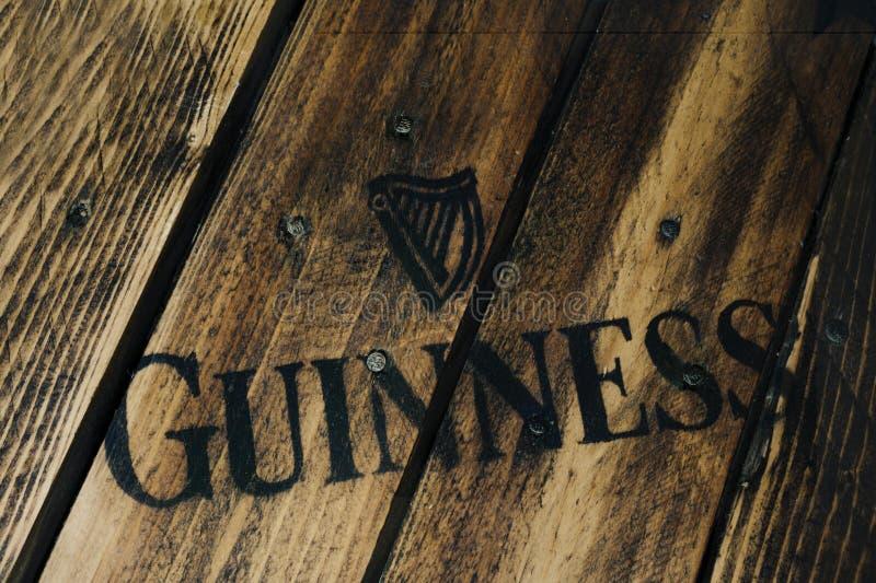 Logo nero della birra di Guinness su legno stagionato rustico fotografia stock