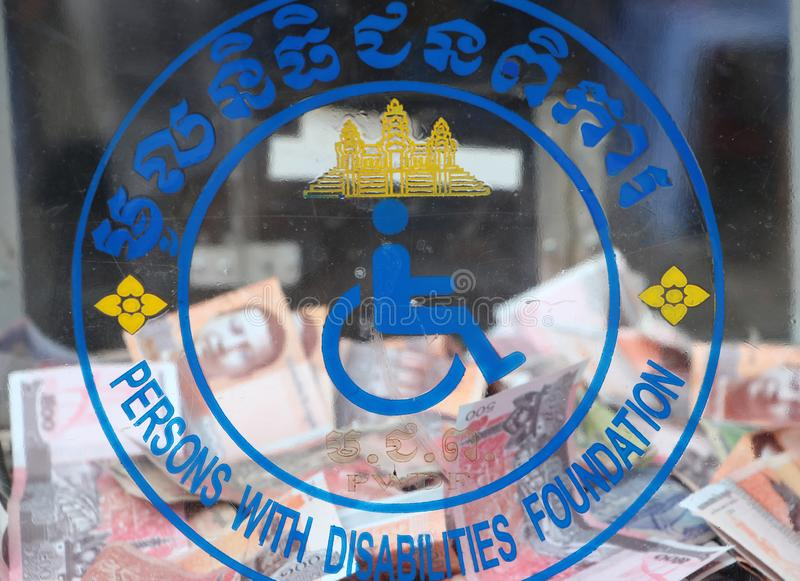 Logo of persons with disabilities foundation of Cambodia on the donation box. And out focus Cambodian money stock photography