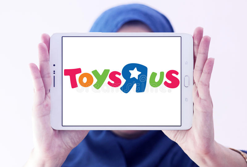 Toys R Us kids store logo. Logo of Toys R Us kids store on samsung tablet holded by arab muslim woman. Toys `R` Us, Inc. is an American toy and juvenile-products royalty free stock photography