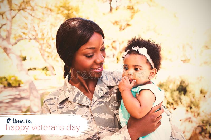 Composite image of logo for veterans day in america hashtag. Logo for veterans day in america hashtag against female soldier carrying daughter at park royalty free stock photo