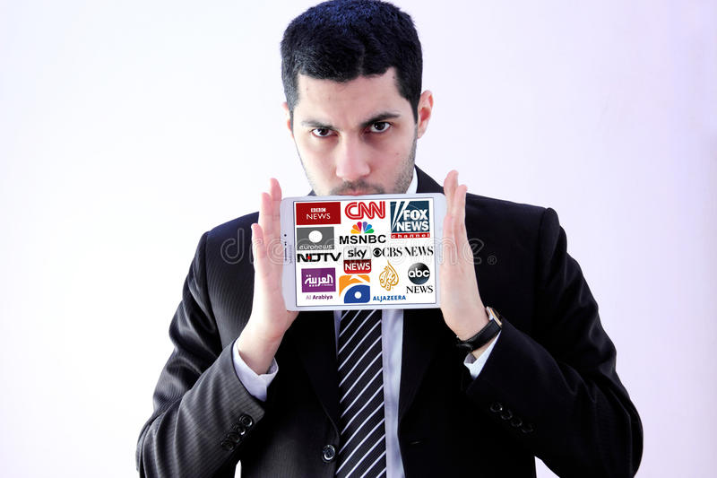 Logos of top famous tv news channels and networks. Arab businessman holding white tablet and logos of top famous tv news channels and networks on display stock images