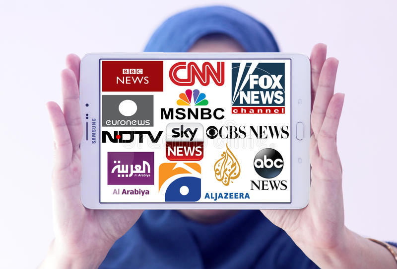 Logos of top famous tv news channels and networks. Arab muslim woman holding white tablet and logos of top famous tv news channels and networks on display royalty free stock photo