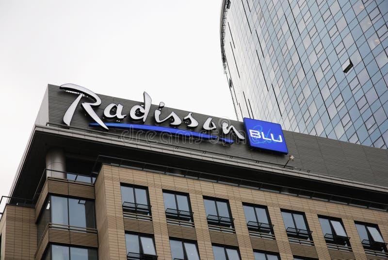 Logotipo azul de la cadena de hoteles de Radisson encima de la nueva fachada del hotel imagenes de archivo