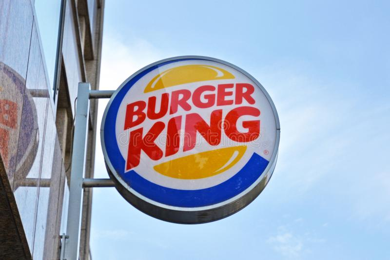 Logotipo da cadeia alimentar de fast food 'Burger King 'do hamburguer que pendura fora na frente do céu azul foto de stock