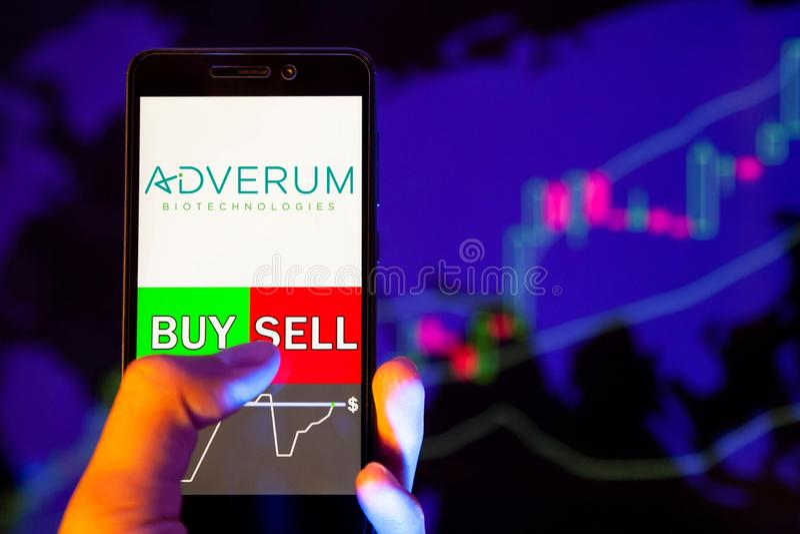 Logotipo da empresa Adverum Biotechnology Inc na tela do smartphone, mão do operador segurando um telefone celular mostrando COMP fotos de stock royalty free